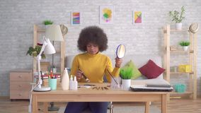 Beautiful african american afro hairstyle girlputting makeup. Beautiful african american girl with an afro hairstyle does make-up in modern apartments stock footage