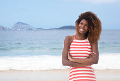 Beautiful african american girl with crazy hairstyle and striped dress at beach Stock Image