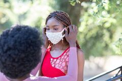 Free Beautiful African-American Girl Helps Her Friend To Put A Face Mask On. Face Covering Is Important To Protect From Stock Photo - 184828360