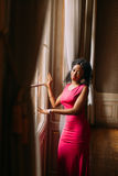 Beautiful African-American girl in red dress posing at the luxurious apartments. Beautiful African-American girl posing in the luxurious apartments stock photography