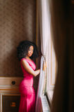 Beautiful African-American girl in red dress posing at the luxurious apartments. Beautiful African-American girl posing in the luxurious apartments royalty free stock photo