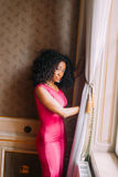 Beautiful African-American girl in red dress posing at the luxurious apartments. Beautiful African-American girl posing in the luxurious apartments stock image