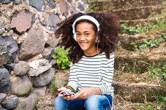 Beautiful african american girl with smart phone and earphones. Royalty Free Stock Photos
