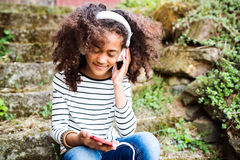 Beautiful african american girl with smart phone and earphones. Stock Photo