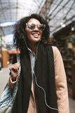 Beautiful African American girl standing on street in earphones. Portrait of cool girl with dark curly hair in royalty free stock images