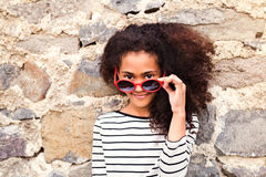 Beautiful african american girl with sunglasses against stone wa Royalty Free Stock Images