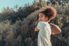 beautiful african american girl throwing rugby ball royalty free stock photo