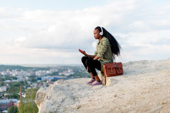 Beautiful african american hipster young woman with smartphone and headphones listening to music over blue cloudy sky Royalty Free Stock Photos