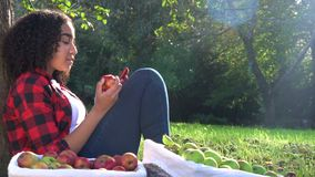 Biracial teenage girl young woman sitting against a tree eating an apple using her mobile cell smart phone stock video footage