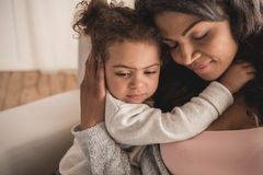 Beautiful african american mother and daughter hugging at home Stock Photography