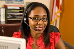 Beautiful African American Receptionist. A beautiful African American receptionist wearing a telephone headset and glasses smiling as she looks toward the camera Royalty Free Stock Photography