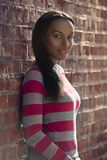 Beautiful african american student woman wearing casual clothes and standing near brick wall outdoors stock photos
