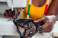Beautiful african american tailor woman sewing laces sexy lingerie in showroom