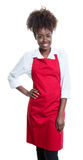 Beautiful african american waitress with curly hair and red apron Royalty Free Stock Photo