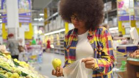 Beautiful african american woman with an afro hairstyle buys fruit in the supermarket stock footage