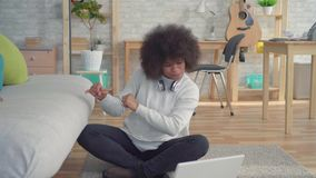 Beautiful african american woman with an afro hairstyle sitting on the floor with a laptop learned about the win stock video
