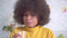 Beautiful african american woman with an afro hairstyle takes a pill and drinks from a glass of water. Close up stock video footage