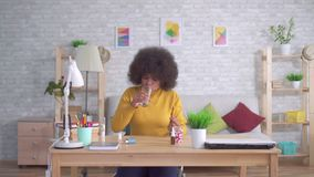 Beautiful african american woman with an afro hairstyle takes a pill and drinks from a glass of water stock video
