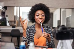 Beautiful african american woman with bright lipstick demonstrating a face brush stock photo