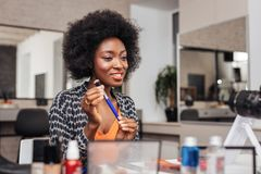 Beautiful african american woman with bright lipstick looking amused. Beauty secrets. Beautiful african american woman with bright lipstick looking amused while stock photo