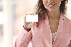 Beautiful African American woman with business card. On blurred background, closeup Royalty Free Stock Image