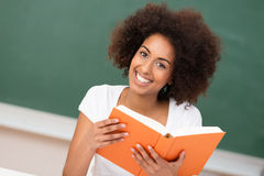 Beautiful African American woman in class. Beautiful African American woman with an afro hairstyle sitting in class at university holding a large textbook royalty free stock images