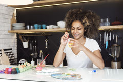 Beautiful African American woman coloring eggs stock image