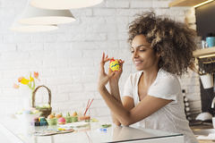 Beautiful African American woman coloring eggs Royalty Free Stock Photo