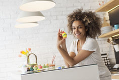 Beautiful African American woman coloring eggs stock photography