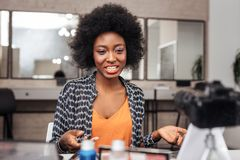 Beautiful african american woman with curly hair showing a brush for concealer royalty free stock photography