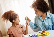 Beautiful African American woman and her daughter coloring Easter eggs. Beautiful African American women and her daughter coloring Easter eggs at the table Stock Images