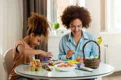 Beautiful African American woman and her daughter coloring Easter eggs Royalty Free Stock Image