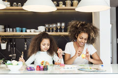 Beautiful African American woman and her daughter coloring Easter eggs in the kitchen stock image