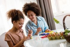 Beautiful African American woman and her daughter coloring Easter eggs. Beautiful African American women and her daughter coloring Easter eggs at the table Royalty Free Stock Image