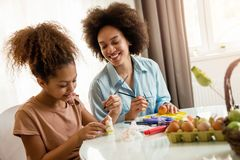 Beautiful African American woman and her daughter coloring Easter eggs. Beautiful African American women and her daughter coloring Easter eggs at the table Stock Photography