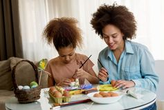 Beautiful African American woman and her daughter coloring Easter eggs. Beautiful African American women and her daughter coloring Easter eggs at the table Royalty Free Stock Images
