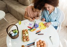 Beautiful African American woman and her daughter coloring Easter eggs. Beautiful African American women and her daughter coloring Easter eggs at the table Stock Image
