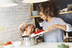 Beautiful African American woman and her daughter cooking. Beautiful African American women and her daughter cooking in the kitchen Stock Photos