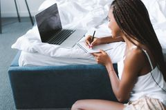 beautiful african american woman with laptop in bed writing royalty free stock photo