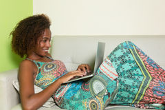 Beautiful african american woman with notebook on couch Stock Photo