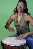 Beautiful African-American woman playing drums Stock Photo