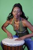 Beautiful African-American woman playing drums. Beautiful African-American woman playing a drum. Taken against a green background. Professional make-up artist stock image