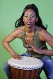 Beautiful African-American woman playing drums. Beautiful African-American woman playing a drum. Taken against a green background. Movement in hands stock photography