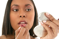 Beautiful African American Woman Putting on Lipgloss. Beautiful 27 year old African American woman putting on lipgloss in small mirror Royalty Free Stock Photography