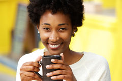 Beautiful african american woman smiling with cup of a coffee Royalty Free Stock Photography