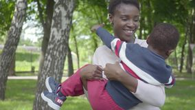 Beautiful African American woman spinning her son in her arms in the green park close up, both laughing. Cute child