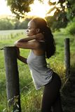 Beautiful African American woman standing at a fence. African American woman standing at a fence in a large field Stock Images