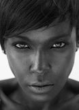 Beautiful african american woman staring. Close up black and white portrait of a beautiful african american woman staring Royalty Free Stock Photo