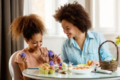 Beautiful African American woman and her daughter coloring Easter eggs. Beautiful African American women and her daughter coloring Easter eggs at the table Royalty Free Stock Photography