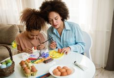 Beautiful African American woman and her daughter coloring Easter eggs. Beautiful African American women and her daughter coloring Easter eggs at the table Stock Photo